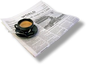 """World"" newspaper with a cup of coffee sitting on top of it"